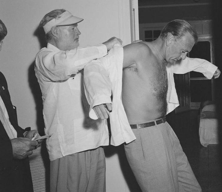 Эрнест Хемингуэй помогает своему другу Гэри Куперу надеть рубашку, Куба, 1956 год.