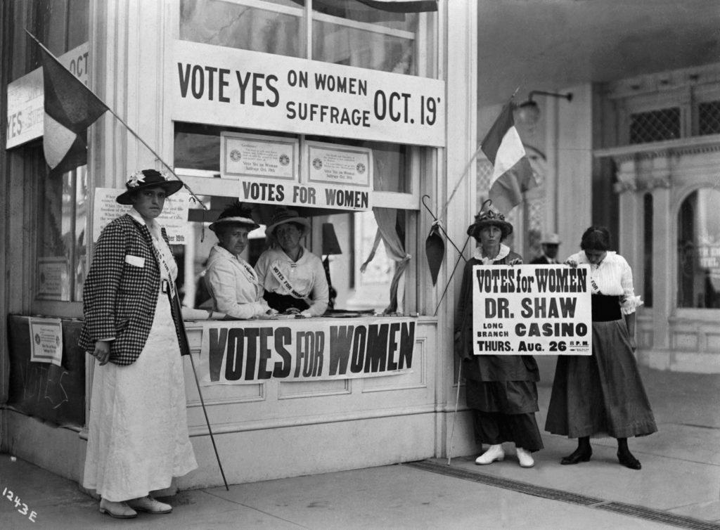 (Оригинальная подпись) 1914 г. - Нью-Йорк: женщины стоят у киоска с информацией об избирательном праве для женщин, призывая людей голосовать «за» в отношении избирательных прав женщин. Феминизм в мировой истории.