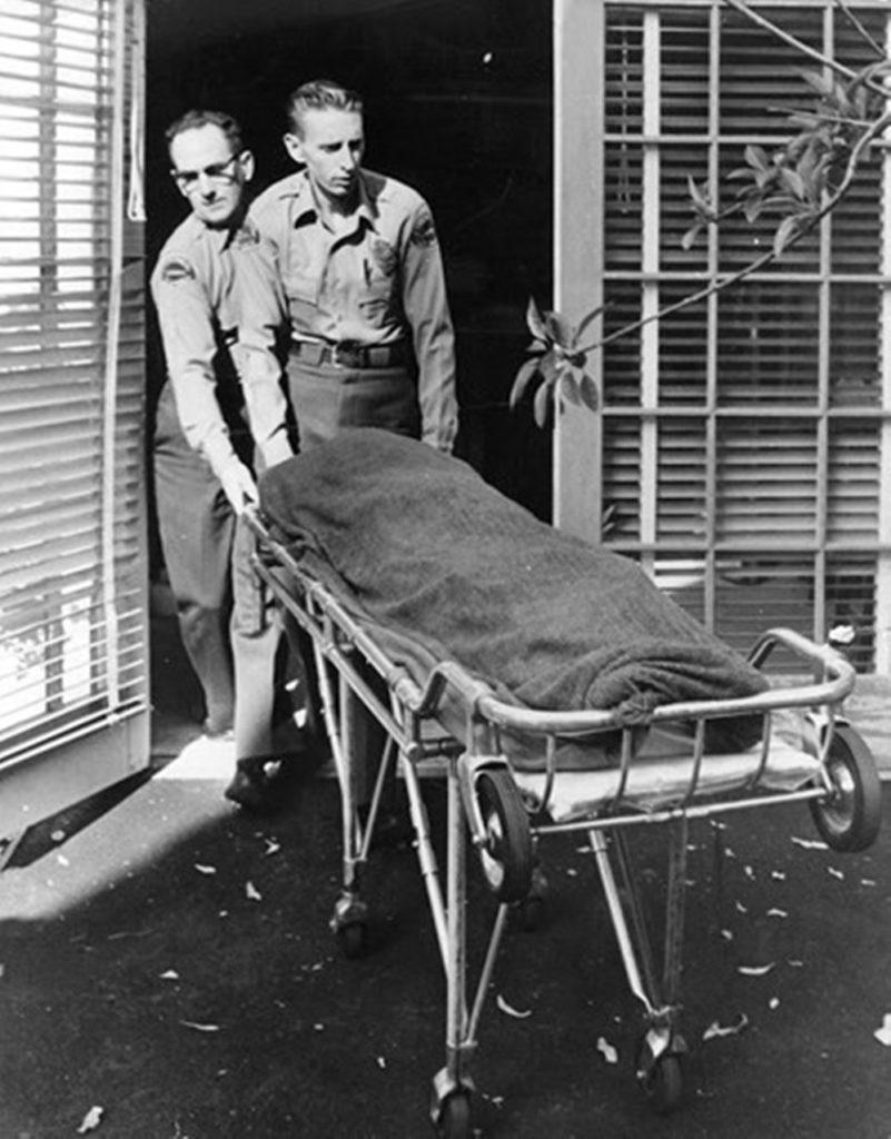 Труп актрисы Мэрилин Монро переносят в морг на носилках двое полицейских.