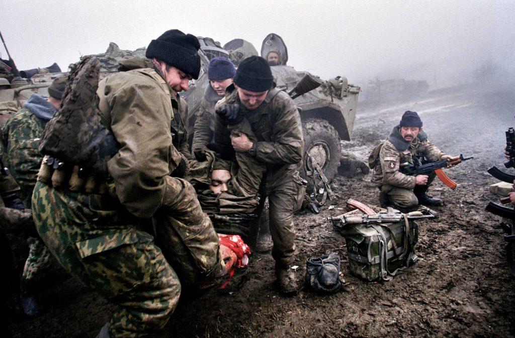 Российские морские пехотинцы уносят тело погибшего товарища во время боёв в селе Центарой, декабрь 1999 года. В сентябре 1999 года началась контртеррористическая операция на Северном Кавказе. Вторая Чеченская война.