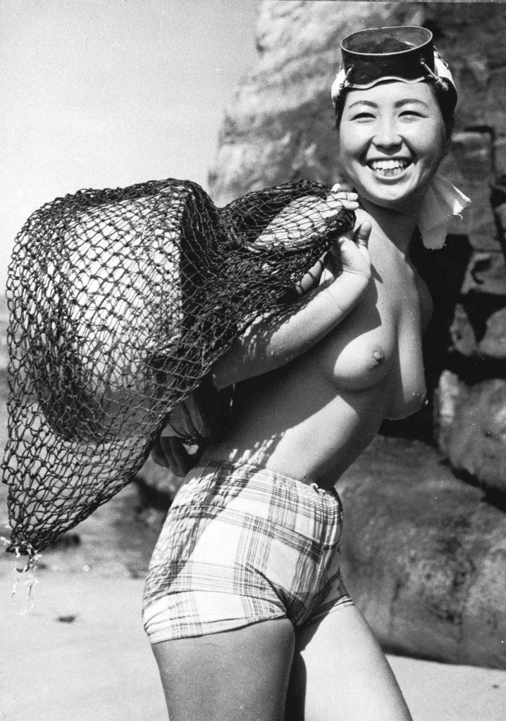 Японский девушка ама возле небольшой рыбацкой деревушки Ондзюку в префектуре Тиба в Японии, август 1959 года.